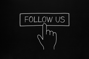 Hand clicking Follow Us button drawn with white chalk on blackboard.